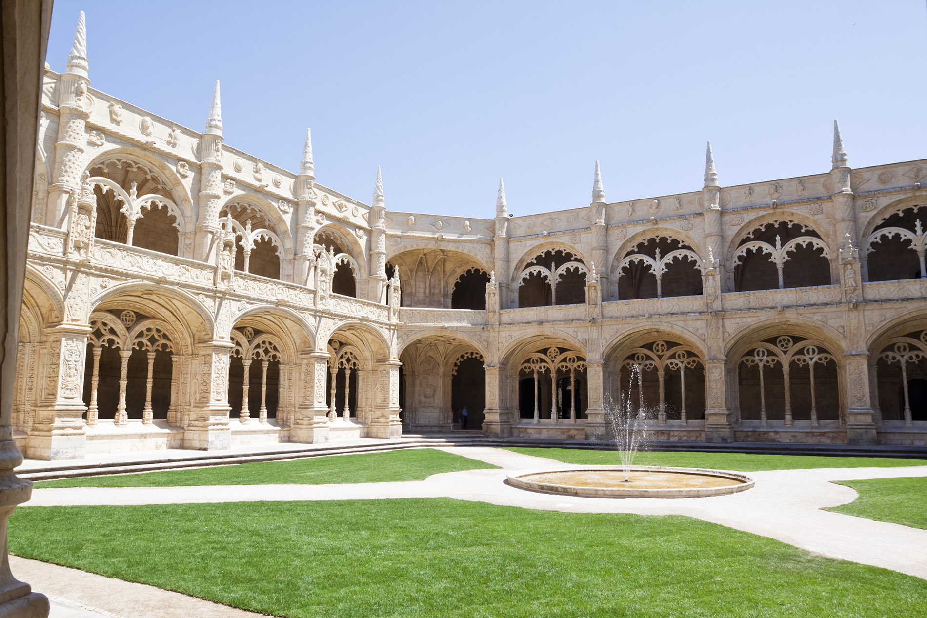 a large stone building with grass in front of a church with Jerónimos Monastery in the background