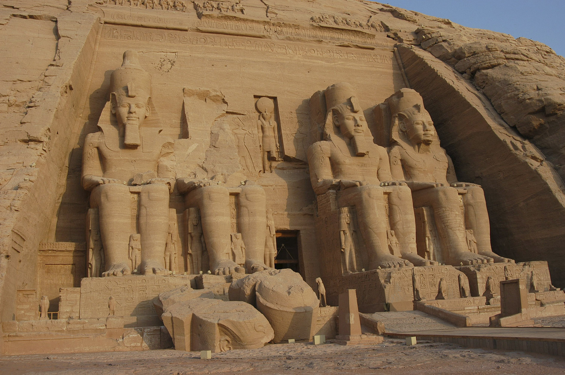 a stone building with Abu Simbel temples in the background