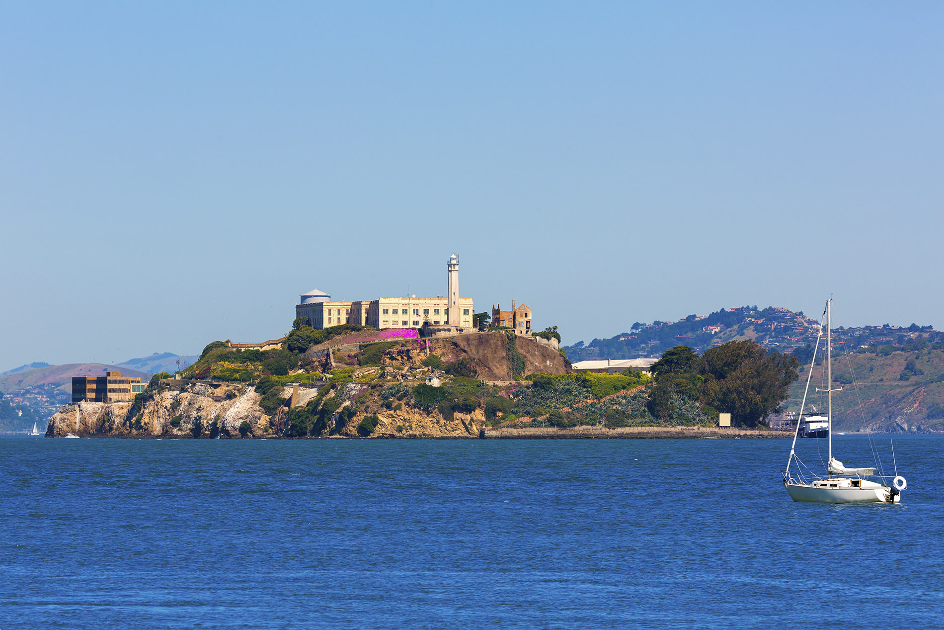 a small boat in a body of water with Alcatraz Island in the background